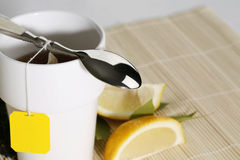 Morning tea closeup. Teabag, cup, spoon and drops of steam Royalty Free Stock Photos