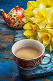 Morning tea. Cup of tea and a bunch of fresh daffodils.Selective focus stock images