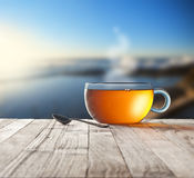 Morning Tea Cup Sky Background. A cup of tea on a rustic wood deck with out of focus sea and sky background Stock Photos