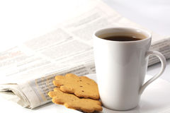 Morning tea drinking. Cup of tea on dish with cookies and newspaper Stock Images
