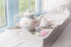Morning tea near a window. Tea pot and a cup. Tender beautiful blue decor Royalty Free Stock Photo