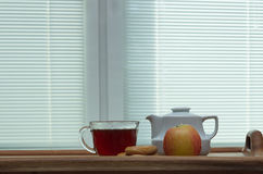 Morning tea on a tray. Tea set with apples on the background of blinds Royalty Free Stock Photo