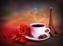 Morning tea in Valentine day. Picture of white cup with morning tea in Valentine day, grunge background, red fresh rose, chocolate candy, decorative Eiffel tower Royalty Free Stock Photos