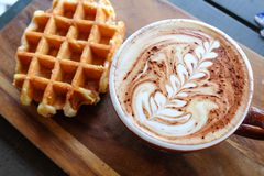 Morning tea. Waffle with a cup of cappuccino on wooden board Royalty Free Stock Photography