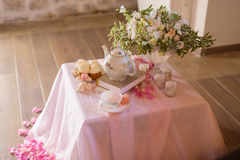Morning tearoom table setting. With flower composition and cakes Stock Image