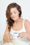 Morning tenderness. Pretty young woman waken up and having coffee in her bed Royalty Free Stock Photography