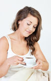 Morning tenderness. Pretty young woman waken up and having coffee in her bed Stock Photography