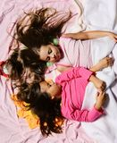 Morning time and childhood concept. Kids with sleepy faces. And long loose hair have rest in bed. Schoolgirls in pink pajamas sleep on colorful pillows, top royalty free stock image