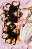 Morning time and childhood concept. Schoolgirls in pink pajamas. Wallow on colorful pillows, top view. Girls lie on white and pink bed sheets. Kids with happy royalty free stock photos