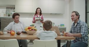 Morning time in a modern kitchen attractive family taking breakfast together mom preparing the table with yummy food dad stock footage