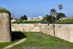 Acco Ancient City Wall. Morning time at the old town of Acco (Acre), Israel. Amongst the green weeds carpet, a path created by thousands of strolls fades into Royalty Free Stock Photos