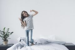 A small black-haired girl is dancing on the bed with a smartphone in her hands and earphones Stock Photography