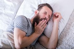 Morning time wake man bed yawning widely. Morning. Time to wake up. Man lying in bed yawning widely with eyes closed. Want to sleep stock photos