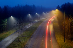 Morning traffic. Light trails of passing cars on a foggy November morning in Oulu, Finland Stock Photography