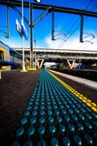 Morning at train station platform with safety dots Royalty Free Stock Images