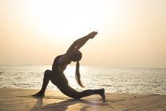 Morning training of yoga on the summer beach stock image