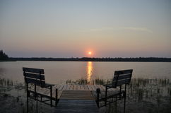 Morning tranquility at sunrise over the lake. The sun rises over a lake,  silhouetting the dock and benches Royalty Free Stock Photo