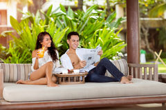 Morning in tropical paradise. Young couple drinking coffee in deck chair Royalty Free Stock Image