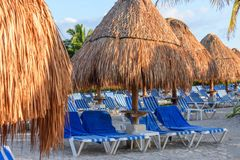 Morning tropical sandy beach with straw umbrellas and lounge chairs. Stock Images