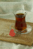 Morning turkish tea in traditional glass with red paper heart, b Stock Photos