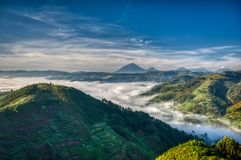 Morning in Uganda with volcanoes in background, fog in the valley and farmlands stretching far. Dramatic sky, valley fog and farmland with Muhavura volcano in stock photography