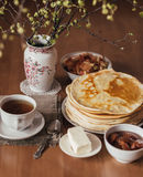 Morning vegetarian breakfast. Stack of delicious homemade pancakes or blini, cup. Of tea, butter and jam in a bowl on wooden table. Vertical toned photo stock image