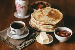 Morning vegetarian breakfast. Stack of delicious homemade pancakes or blini, cup. Of tea, butter and jam in a bowl on wooden table. Toned photo royalty free stock image