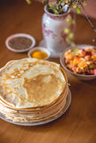 Morning vegetarian breakfast. Stack of delicious homemade pancakes or blini. On wooden table. Vertical toned photo royalty free stock image