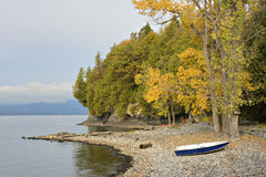 Morning on Vermont shore with boats on rocks Royalty Free Stock Photo