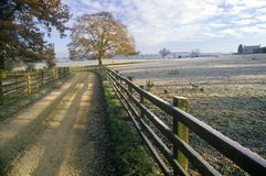Morning view of a country road and wood fence in Upper Brails, England Royalty Free Stock Image