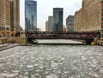 Morning view of frozen Chicago River and surrounding cityscape during heavy snowfall. Royalty Free Stock Images