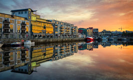 Morning view on Galway Dock with boats. Morning view on row of buildings and fishing boats in Galway Dock with sky reflected in the water, HDR image Royalty Free Stock Image