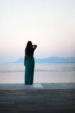 Morning view at the infinity pool. Classy lady gazing at the horizon on the edge of an infinity pool. The woman is wearing a beautiful long turquoise dress Stock Image