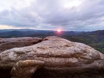 Morning view over cracked sandstone cliff into forest valley, Sun hiddein in heavy clouds  at horizon. Stock Photography
