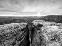 Morning view over cracked sandstone cliff into forest valley, Sun hiddein in heavy clouds  at horizon. Royalty Free Stock Images