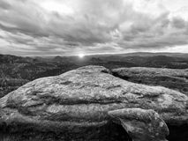 Morning view over cracked sandstone cliff into forest valley, Sun hiddein in heavy clouds  at horizon. Royalty Free Stock Image