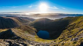 Morning view from Sharp Edge on Blencathra, Lake District, Cumbria with lake tarn and cloud inversion over mountains in the. Distance stock photography