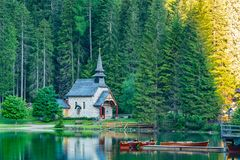 Morning view of small old church at the bank of Lake Braies. In South Tyrol, Italy Royalty Free Stock Image