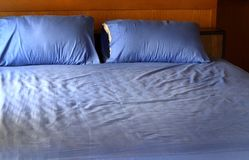 Morning view of an unmade bed with crumpled blue bed linens. And no people Stock Photo