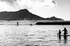 Morning in Waikiki. Waikiki, Hawaii, USA - Sept. 5, 2015: Black and white photo of early morning local recreational activites and a fishing teaching moment in stock photos