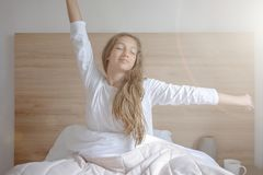 Young woman waking up in her bedroom, sitting on the bed stretching arms royalty free stock photography
