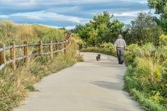 Morning walk with dog  on bike trail Royalty Free Stock Image