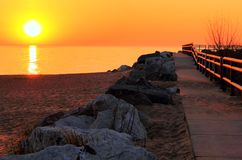 Morning Walk. A gorgeous Great Lakes sunrise burns off the morning fog and a new day has begun. Lexington State Harbor. Lexington, Michigan Stock Photo