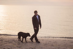 Morning walk of man an dog. Young caucasian male walking with dog on the morning beach, sunset on the sea or ocean and man with black labrador puppy Stock Image