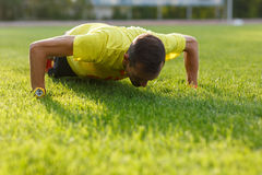 Morning warm-up sporty athletic guy. Man doing push-ups Royalty Free Stock Photography