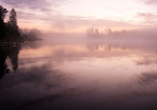 Morning water fog sky. Morning nature scene (landscape): fog (mist) reflected in the water surface (lake, river, pobd) along with trees and shore. The Seliger Royalty Free Stock Photo