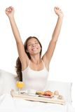 Morning woman in bed with breakfast. Happy woman stretching in bed in the morning with breakfast tray. Asian / Caucasian woman on white background Stock Image