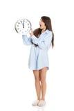 Morning woman in big shirt holding clock. Stock Image
