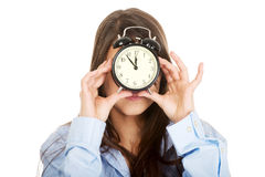 Morning woman in big shirt holding clock. Royalty Free Stock Images