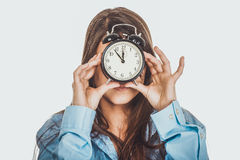 Morning woman in big shirt holding clock. Royalty Free Stock Image